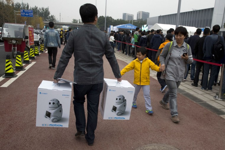 A man walks with boxes of companion robots outside the venue for the World Robot Conference in Beijing, China, Friday, Oct. 21, 2016. The conference showcased China's burgeoning robot industry as the nation seeks to increase the use of robots in its manufacturing and service industries. (AP Photo/Ng Han Guan)
