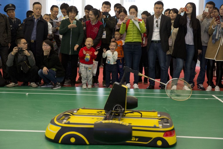 Children cheer on a robot that plays badminton during the World Robot Conference in Beijing, China, Friday, Oct. 21, 2016. The conference showcased China's burgeoning robot industry as the nation seeks to increase the use of robots in its manufacturing and service industries. (AP Photo/Ng Han Guan)