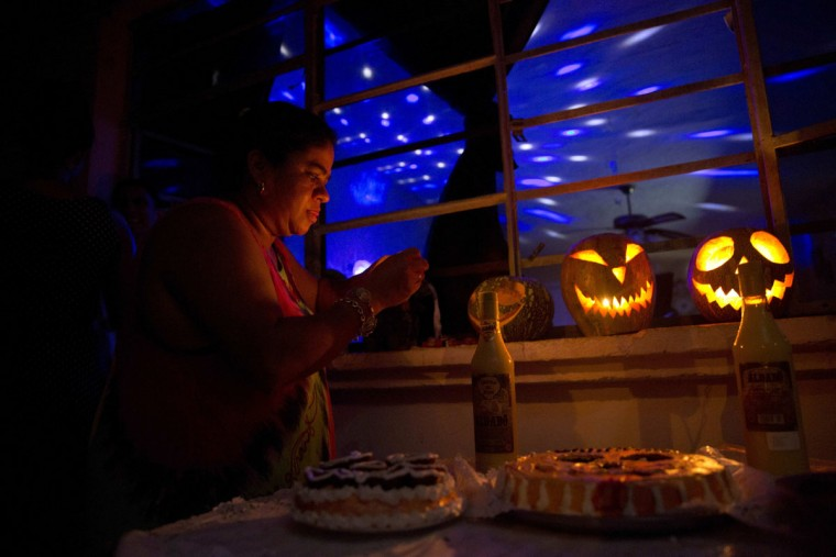Marilyn Alvarez lights jack-o-lanterns during a Halloween party at a residence in Havana, Cuba, late Friday, Oct. 28, 2016. Inspired by pirated U.S. movies and television shows, young Cubans are turning American-style Halloween parties into the island's latest trend. (AP Photo/Ramon Espinosa)