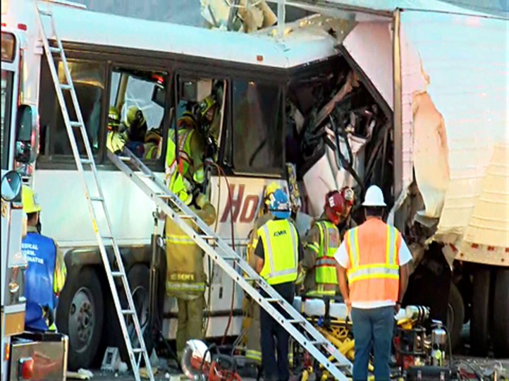 This photo provided by KESQ News Channel 3/CBS Local 2 shows the scene of crash between a tour bus and a semi-truck on Interstate 10 in Desert Hot Springs, near Palm Springs, in California's Mojave Desert Sunday, Oct. 23, 2016. Multiple deaths and injuries were reported. (KESQ NewsChannel 3/CBS Local 2 via AP)