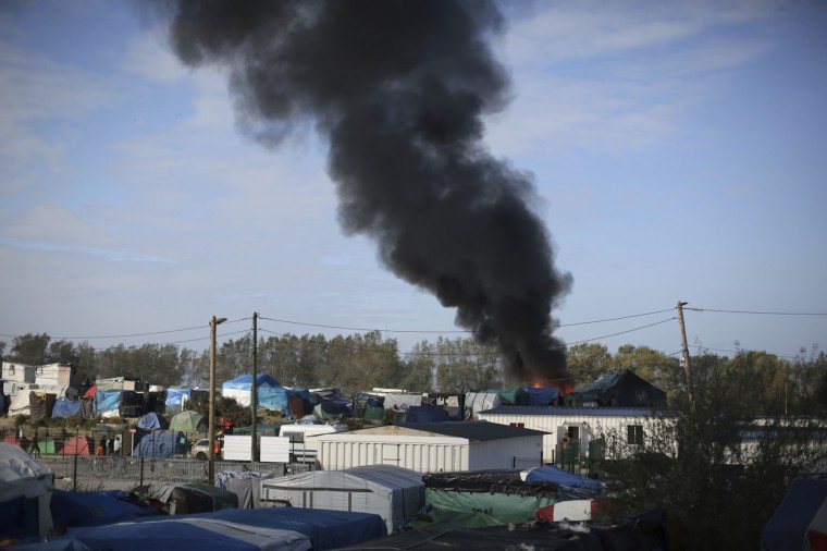 "Smoke rises as a wooden house burns in the makeshift migrant camp known as ""the jungle"" near Calais, northern France, Tuesday, Oct. 25, 2016. Crews have started dismantling the migrant camp in France after the process to clear the camp began in earnest on Monday. (AP Photo/Thibault Camus)"