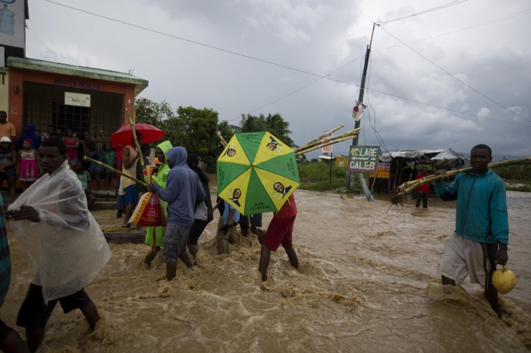 People wade through a street flooded by a nearby river overflowing from the heavy rains caused by Hurricane Matthew, in Leogane, Haiti, Wednesday, Oct. 5, 2016. Rescue workers in Haiti struggled to reach cutoff towns and learn the full extent of the death and destruction caused by Hurricane Matthew as the storm began battering the Bahamas on Wednesday and triggered large-scale evacuations along the U.S. East Coast. ( AP Photo/Dieu Nalio Chery)