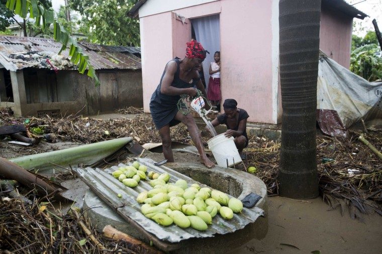 A woman pulls drinking water from a well near her home flooded by Hurricane Matthew, in Leogane, Haiti, Wednesday, Oct. 5, 2016. At least 11 deaths were blamed on the powerful storm during its weeklong march across the Caribbean, five of them in Haiti. But with a key bridge washed out, roads impassable and phone communications down, the western tip of Haiti was isolated and there was no full accounting of the dead and injured in Matthew's wake. (AP Photo/Dieu Nalio Chery)
