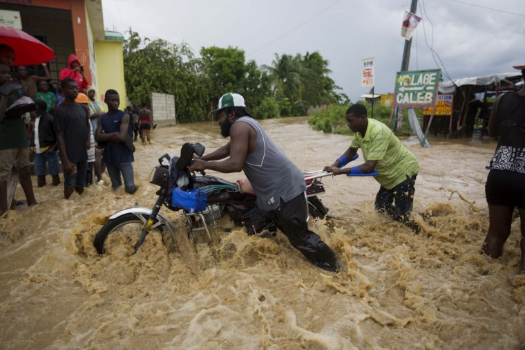 Two men push a motorbike through a street flooded by a nearby river that overflowed from heavy rains caused by Hurricane Matthew, in Leogane, Haiti, Wednesday, Oct. 5, 2016. Rescue workers in Haiti struggled to reach cutoff towns and learn the full extent of the death and destruction caused by Hurricane Matthew as the storm began battering the Bahamas on Wednesday and triggered large-scale evacuations along the U.S. East Coast. (AP Photo/Dieu Nalio Chery)