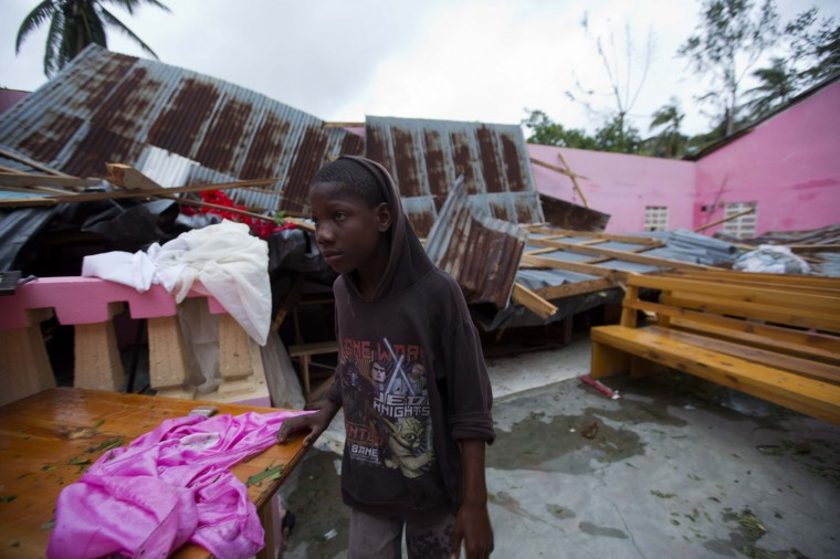 A boy stands inside a church after it was damaged by Hurricane Matthew in Saint-Louis, Haiti, Wednesday, Oct. 5, 2016. Rescue workers in Haiti struggled to reach cutoff towns and learn the full extent of the death and destruction caused by Hurricane Matthew as the storm began battering the Bahamas on Wednesday and triggered large-scale evacuations along the U.S. East Coast. (AP Photo/Dieu Nalio Chery)