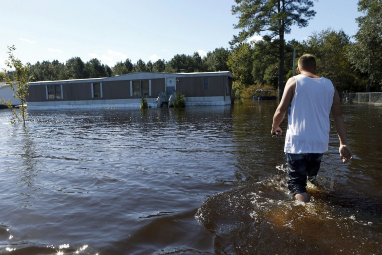 Elmer McDonald makes his way through a strong current in his front yard as he returns to his mobile home for the first time to inspect damage caused by floodwaters associated with Hurricane Matthew on Thursday, Oct. 13, 2016, in Lumberton, N.C. About 1,200 Lumberton residents had to be evacuated by boat and plucked from their roofs by helicopters as the river crested; McDonald was one of thousands who evacuated. (AP Photo/Brian Blanco)