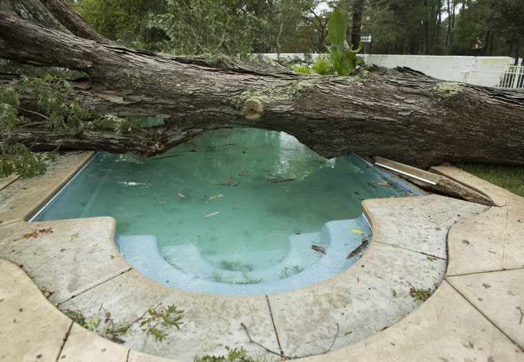 A large oak tree felled by Hurricane Matthew lies across Candy Gray's pool and on to the detached garage behind her house in the Birdneck Point section of Virginia Beach, Va., as Hurricane Matthew passed Sunday morning, Oct 9, 2016. Forecasters said North Carolina and Virginia could get even more rain and warned of the danger of life-threatening flooding through Monday night. (L. Todd Spencer/The Virginian-Pilot via AP)