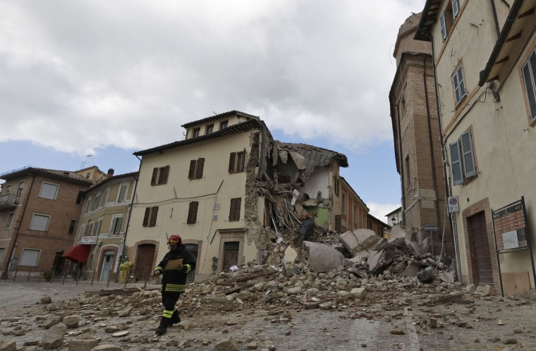A firefighter walks away of the collapsed bell tower of the Santa Maria in Via church in the town of Camerino, in central Italy, Thursday, Oct 27, 2016, after a 5.9 earthquake destroyed part of the town. (AP Photo/Alessandra Tarantino)