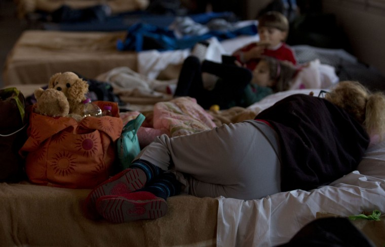 Residents rest in a warehouse where they found a temporary shelter in the town of Camerino, central Italy, Thursday, Oct. 27, 2016, after a 5.9 earthquake destroyed part of the town. Authorities scrambled to find housing Thursday for thousands of people displaced by a pair of strong earthquakes that struck the same region of central Italy hit by a deadly quake in August, hoping to prevent a second night for them on the street or in cars. (AP Photo/Alessandra Tarantino)