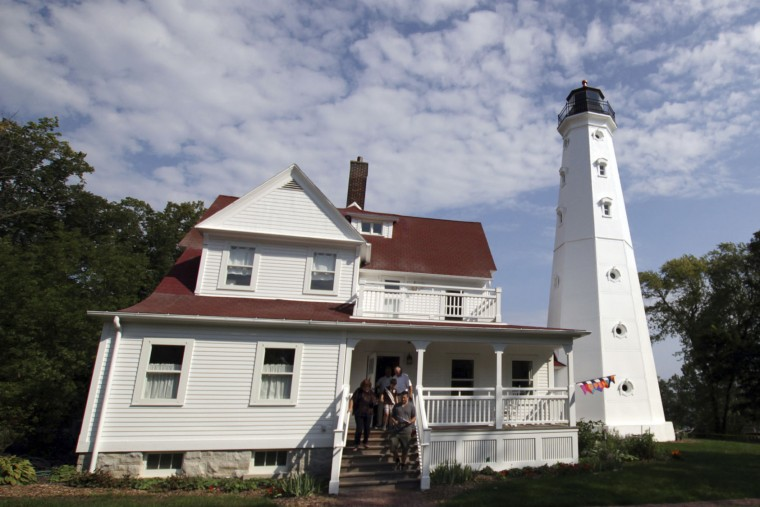In this photo taken Sunday, Sept. 25, 2016, a family walks out of the North Point Lighthouse in Milwaukee after a tour. About 120 lighthouses no longer critical to the U.S. Coast Guard in 22 states and Puerto Rico have been acquired at no cost by government entities and nonprofits, or sold to private individuals eager to preserve the landmarks and tap into their tourism potential since they became available under the National Historic Lighthouse Preservation Act of 2000. (AP Photo/Carrie Antlfinger)