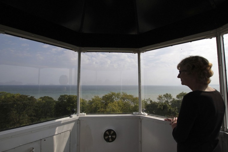 In this photo taken Sunday, Sept. 25, 2016, Marian Gladieux, of Oregon, Ohio, looks out the tower of the North Point Lighthouse in Milwaukee. About 120 lighthouses no longer critical to the U.S. Coast Guard in 22 states and Puerto Rico have been acquired at no cost by government entities and nonprofits, or sold to private individuals eager to preserve the landmarks and tap into their tourism potential since they became available under the National Historic Lighthouse Preservation Act of 2000. (AP Photo/Carrie Antlfinger)
