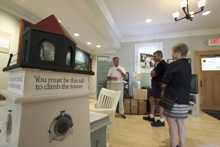 In this photo taken Sunday, Sept. 25, 2016, Michael Connor, left, gives tours at the North Point Lighthouse in Milwaukee. A group of volunteers spent about a decade acquiring and renovating the living quarters and tower, opening it to the public in 2007. (AP Photo/Carrie Antlfinger)