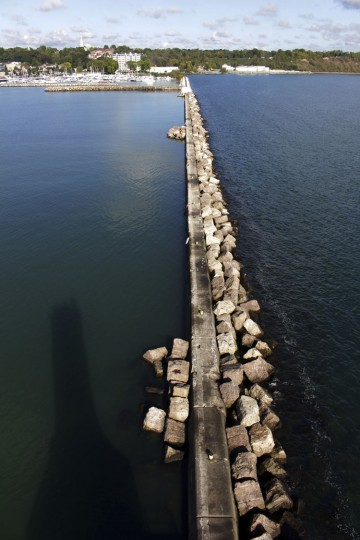 This photo taken October 3, 2016, shows the shadow of the light head tower on the Port Washington, Wis. breakwater. The city is in the process of acquiring it, with plans to raise and spend $1.5 million to restore. About 120 lighthouses no longer critical to the U.S. Coast Guard in 22 states and Puerto Rico have been acquired at no cost by government entities and nonprofits, or sold to private individuals eager to preserve the landmarks and tap into their tourism potential since they became available under the National Historic Lighthouse Preservation Act of 2000. (AP Photo/Carrie Antlfinger)