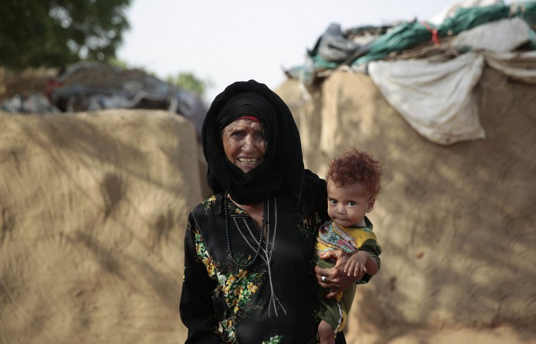 In this photo taken on Friday, Oct. 7, 2016, an elderly woman holds her grandson as she stands outside of her hut at a camp for internally displaced people near the town of Abs, located on Yemen's western coastal plain below towering desert mountains. Hundreds of Yemenis fleeing war are now living in tents and mud-brick shelters scattered across a cornfield, where they buried the remains of loved ones they carried with them when they escaped. (AP Photos / Hani Mohammed)