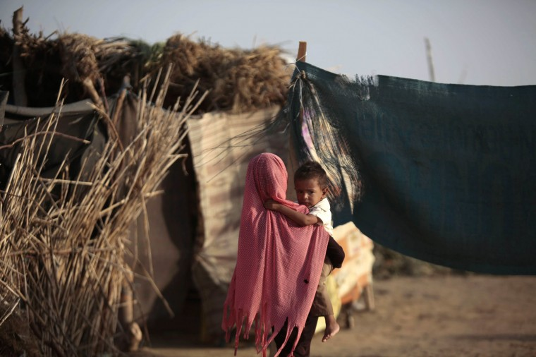 In this photo taken on Thursday, Oct. 6, 2016, a displaced girl holds her brother at a camp for internally displaced people near the town of Abs, located on Yemen's western coastal plain below towering desert mountains. Hundreds of Yemenis fleeing war are now living in tents and mud-brick shelters scattered across a cornfield, where they buried the remains of loved ones they carried with them when they escaped. (AP Photos / Hani Mohammed)