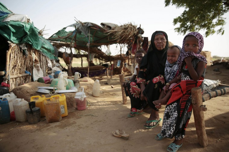 In this photo taken on Friday, Oct. 7, 2016, a family gather in their hut at a camp for internally displaced people near the town of Abs, located on Yemen's western coastal plain below towering desert mountains. Hundreds of Yemenis fleeing war are now living in tents and mud-brick shelters scattered across a cornfield, where they buried the remains of loved ones they carried with them when they escaped. (AP Photos / Hani Mohammed)