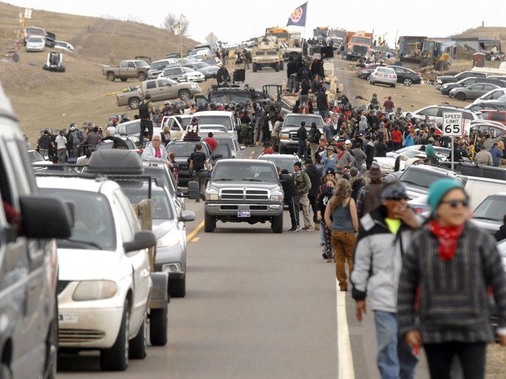 An exodus of Dakota Access Pipeline protesters move south on Highway 1806 as a line of law enforcement slowly push the protest effort from the Front Line Camp to the Oceti Wakoni overflow camp a few miles down the road in Morton County, N.D., Thursday, Oct. 27, 2016. (Mike McCleary/The Bismarck Tribune via AP)