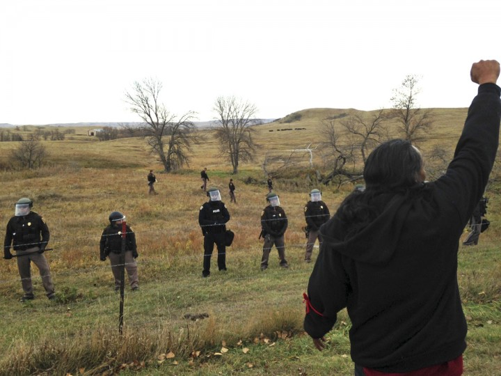 A Dakota Access pipeline protester defies law enforcement officers who are trying to force them from a camp on private land in the path of pipeline construction, Thursday, Oct. 27, 2016 near Cannon Ball, N.D. Soldiers and law enforcement officers dressed in riot gear began arresting protesters who had set up a camp on private land to block construction of the Dakota Access oil pipeline. (AP Photo/James MacPherson)