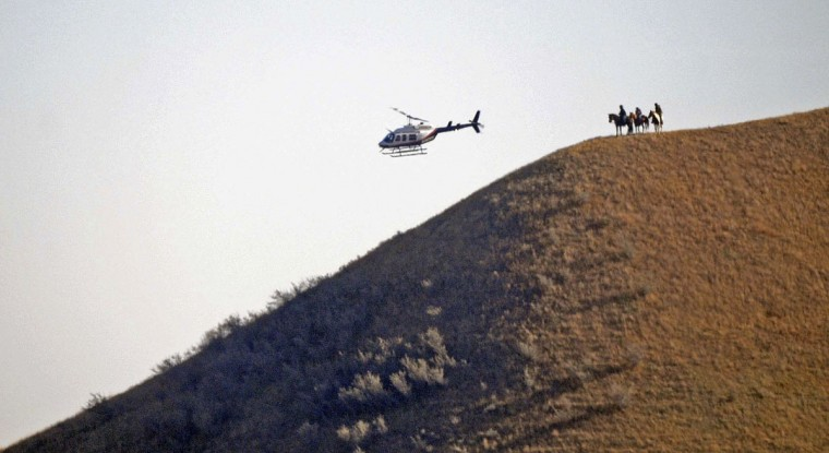 Three people on horseback watch from a hillside as a helicopter sweeps by on Wednesday, Oct. 26, 2016, near the New Camp on Pipeline Easement in southern Morton County, ND.The prospect of a police raid on an encampment protesting the Dakota Access pipeline faded as night fell Wednesday, with law enforcement making no immediate move after protesters rejected their request to withdraw from private land. Activists fear the nearly 1,200-mile pipeline could harm cultural sites and drinking water for the Standing Rock Sioux tribe. (Tom Stromme/The Bismarck Tribune via AP)