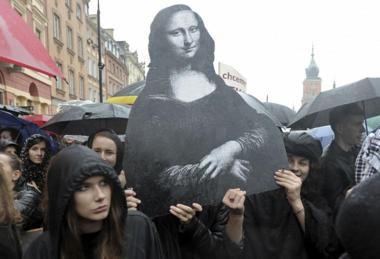 "Women carry a reproduction of the famous Leonardo Da Vinci painting, Mona Lisa, symbolizing femininity, as thousands of protesters gather at Castle Square during a nationwide ""Black Monday"" strike to protest a legislative proposal for a total ban on abortion, in Warsaw, Poland, Monday, Oct. 3, 2016. Massive protests were held in the rain in the streets of Warsaw, Gdansk, Wroclaw and elsewhere across the largely Catholic nation led by a conservative government. (AP Photo/Alik Keplicz)"