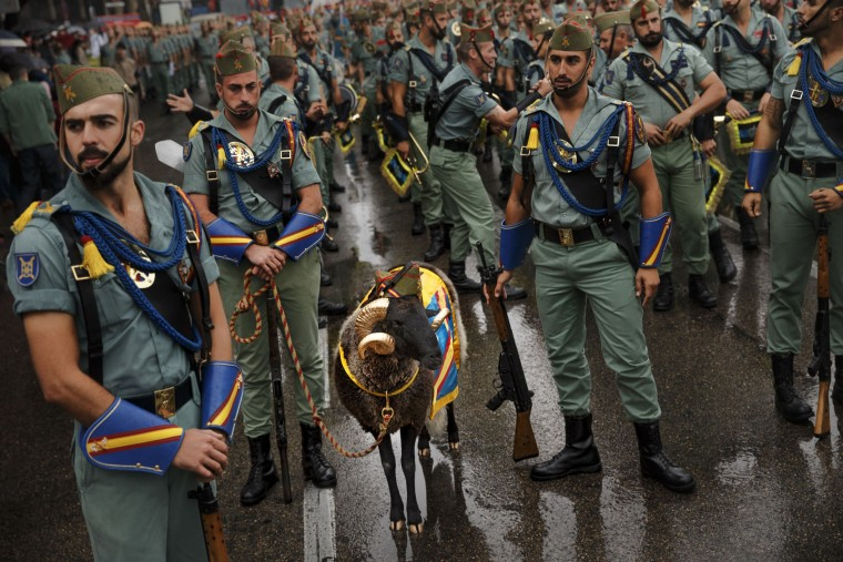 Members of La Legion, an elite unit of the Spanish Army, including a goat they use as a pet wait for the start of a military parade as they celebrate a holiday known as 'Dia de la Hispanidad' or Hispanic Day in Madrid, Wednesday, Oct. 12, 2016. Almost a year into Spain's political deadlock, the country is celebrating its National Day with a military parade of over 3,000 soldiers marching through Madrid and aircraft drawing trails of red and yellow smoke in the sky to represent the flag. (AP Photo/Daniel Ochoa de Olza)