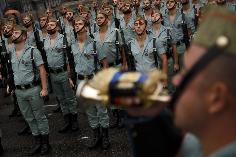 Members of La Legion, an elite unit of the Spanish Army, prepare for a military parade to celebrate a holiday known as 'Dia de la Hispanidad' or Hispanic Day in Madrid, Wednesday, Oct. 12, 2016. Almost a year into Spain's political deadlock, the country is celebrating its National Day with a military parade of over 3,000 soldiers marching through Madrid and aircraft drawing trails of red and yellow smoke in the sky to represent the flag. (AP Photo/Daniel Ochoa de Olza)