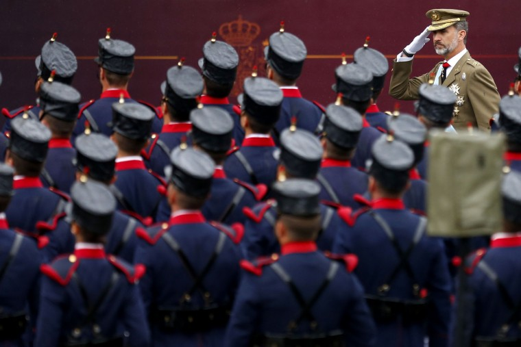 """Spain's King Felipe, right, salutes as he reviews an honor guard at a military parade during a national holiday known as """"Dia de la Hispanidad"""" or Hispanic Day, in Madrid, Wednesday, Oct. 12, 2016. Almost a year into Spain's political deadlock, the country is celebrating its National Day with a military parade of over 3,000 soldiers marching through Madrid and aircraft drawing trails of red and yellow smoke in the sky to represent the flag. (AP Photo/Francisco Seco)"""