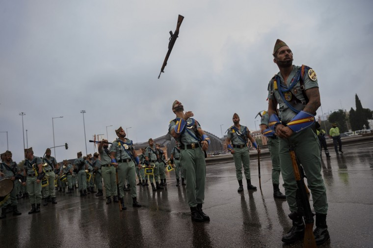 A member of La Legion, an elite unit of the Spanish Army, juggles his weapon before a military parade as they celebrate a holiday known as 'Dia de la Hispanidad' or Hispanic Day in Madrid, Wednesday, Oct. 12, 2016. Almost a year into Spain's political deadlock, the country is celebrating its National Day with a military parade of over 3,000 soldiers marching through Madrid and aircraft drawing trails of red and yellow smoke in the sky to represent the flag. (AP Photo/Daniel Ochoa de Olza)