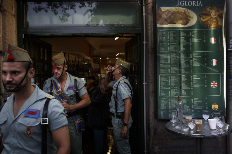 A member of La Legion, an elite unit of the Spanish Army, drinks in a bar before a military parade as they celebrate a holiday known as 'Dia de la Hispanidad' or Hispanic Day in Madrid, Wednesday, Oct. 12, 2016. Almost a year into Spain's political deadlock, the country is celebrating its National Day with a military parade of over 3,000 soldiers marching through Madrid and aircraft drawing trails of red and yellow smoke in the sky to represent the flag. (AP Photo/Daniel Ochoa de Olza)