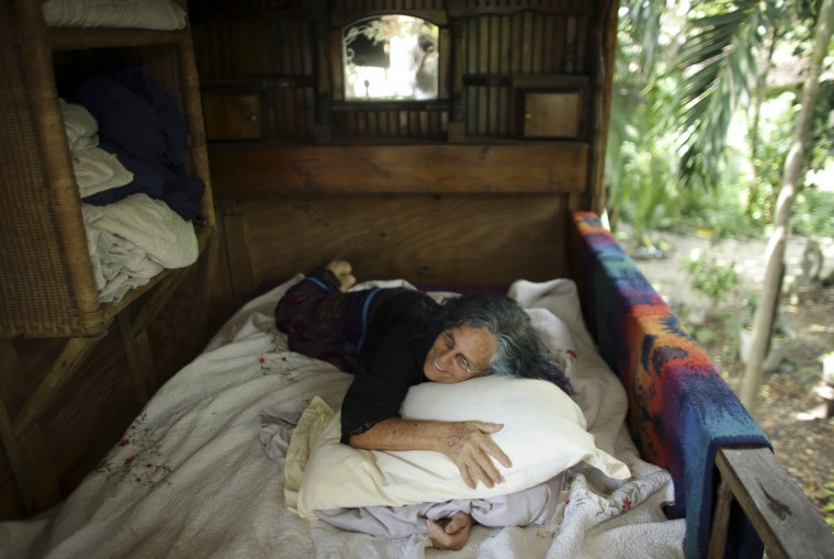 In this Monday, Sept. 19, 2016 photo, Shawnee Chasser poses for a photograph in her treehouse in Miami. The 65-year-old grandmother who protested the Vietnam war and nuclear weapons is fighting county government to keep it. Miami-Dade County code inspectors recently declared that the treehouse is unfit for human habitation and ordered it torn down. (AP Photo/Lynne Sladky)