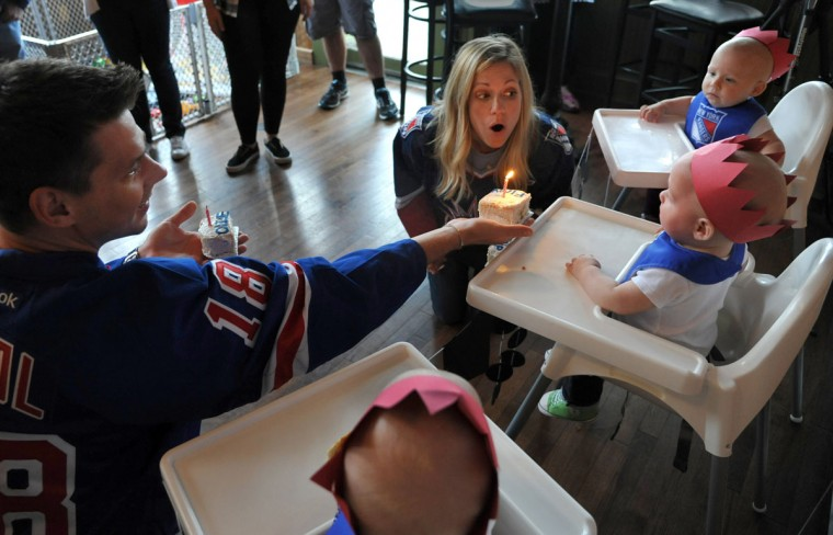 Thomas and Kristen Hewitt of Hampden offer the triplets their first taste of birthday cake after Kristen blows out the candles. The triplets, from front to back, Ollie, Finn and Trip, celebrated with family and friends at Cafe Hon. The identical triplets turned one on Oct. 6. (Amy Davis/ Baltimore Sun)
