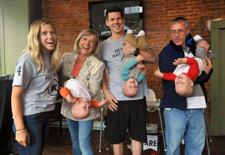 Thomas and Kristen Hewitt of Hampden pose for photos with Kristen's parents, Kathy and Jim Stantz, who moved to Baltimore from Ohio to help the Hewitts with the triplets. The identical triplets, from left, Ollie, Finn and Trip, turned one on Oct. 6. (Amy Davis/ Baltimore Sun)