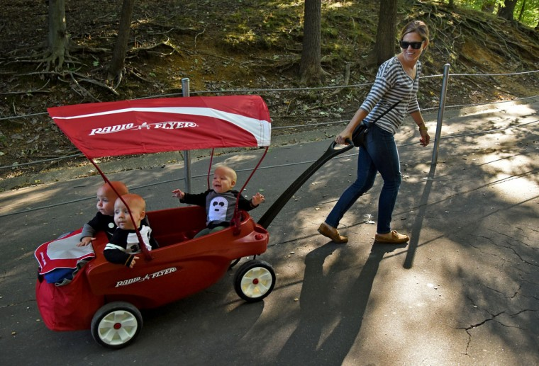 "Clockwise from front, Trip, Ollie and Finn, visit the Baltimore Zoo with their mom, Kristen Hewitt, and her parents, Jim and Kathy Stantz. Kristen said this three-seat wagon has been a ""game changer,"" because it allows her to take the triplets on errands by herself. (Amy Davis/ Baltimore Sun)"