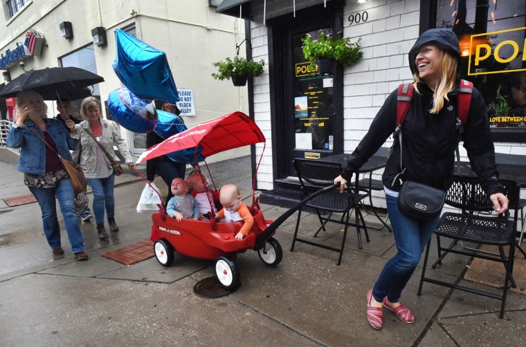 Kristen Hewitt of Hampden pulls the triplets home, after celebrating their first birthday with family and friends at Cafe Hon. The three-seat wagon enables her to do errand with the triplets by herself, but here family and friends help her carry the party paraphernalia home. (Amy Davis/ Baltimore Sun)