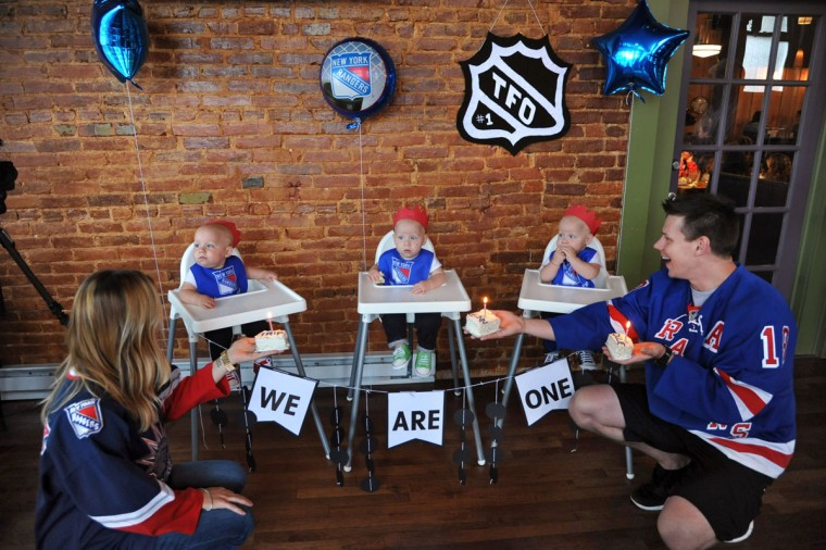 Thomas and Kristen Hewitt of Hampden show the triplets their birthday cake as they sing Happy Birthday. The identical triplets, from left, Trip, Finn and Ollie, turned one on Oct. 6. (Amy Davis/ Baltimore Sun)