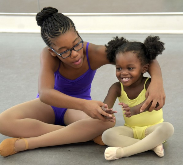 In the creative movement class for young children, Naima Eggleston, 11, a Level IV student, shows Brielle Williams how to curve her arms as though she's holding a beach ball. (Algerina Perna/Baltimore Sun)