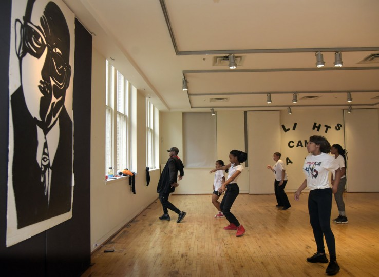 "Hip Hop teacher Tyone Pompey demonstrates Hip Hop moves for his class as they practice next to a poster of American composer and Jazz legend James Hubert ""Eubie"" Blake. (Algerina Perna/Baltimore Sun)"