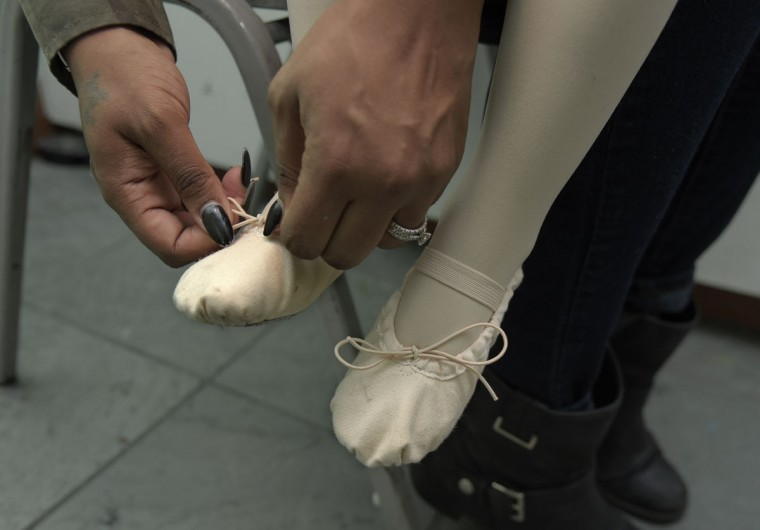 Sheria Washington from Parkville ties the ballet slippers for her daughter, Drew Washington, 3, before the creative movement class. (Algerina Perna/Baltimore Sun)