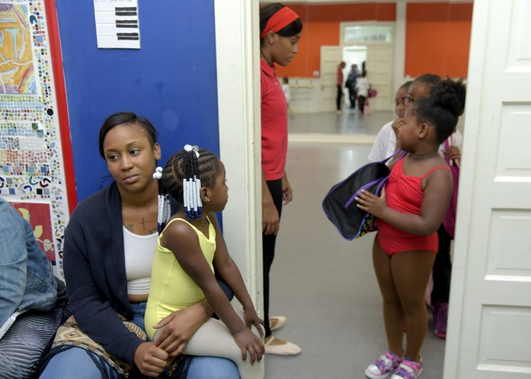 Deborah Thompson holds her daughter Madison, 4, on her lap as she waits for Madison's creative movement class to begin. Standing in the doorway is dance instructor, Falisha Massey. (Algerina Perna/Baltimore Sun)
