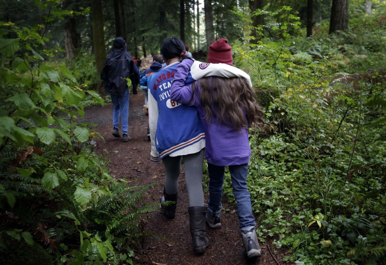 In this Oct. 6, 2016, photo, two Outdoors School students walk arm-in-arm through the dense forest to an Outdoors School lesson at Camp Howard in Mount Hood National Forest near Corbett, Ore. The outdoor education is unique to Oregon and is a rite-of-passage for public school students that's meant to instill a respect for nature in each generation; studies show it improves attendance and boosts test scores. (AP Photo/Don Ryan)