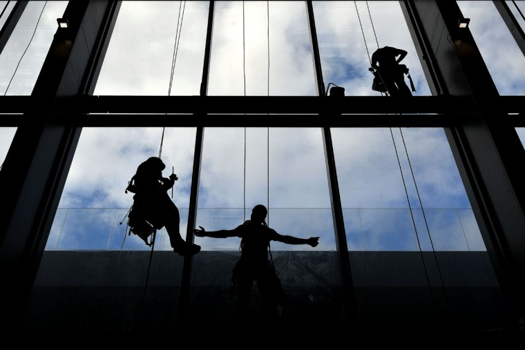 "Workers clean the windows of the new convention center named ""The cloud"" (""La Nuvola"" in Italian) designed by Italian architect Massimiliano Fuksas on October 19, 2016 in the Eur business district in Rome. The congress center will be inaugurated on October 29, 2016. (ALBERTO PIZZOLI/AFP/Getty Images)"