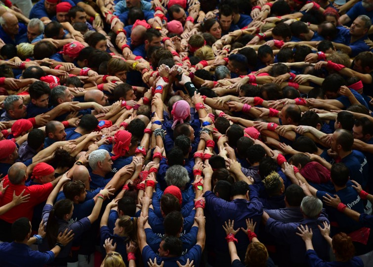 "Members of the ""Colla Xiquets del Serrallo"" human tower team form a ""castell"" during the XXVI human towers, or castells, competetion in Tarragona on October 1, 2016. These human towers, built traditionally in festivals within Catalonia, gather several teams that attempt to build and dismantle a tower structure. (LLUIS GENE/AFP/Getty Images)"