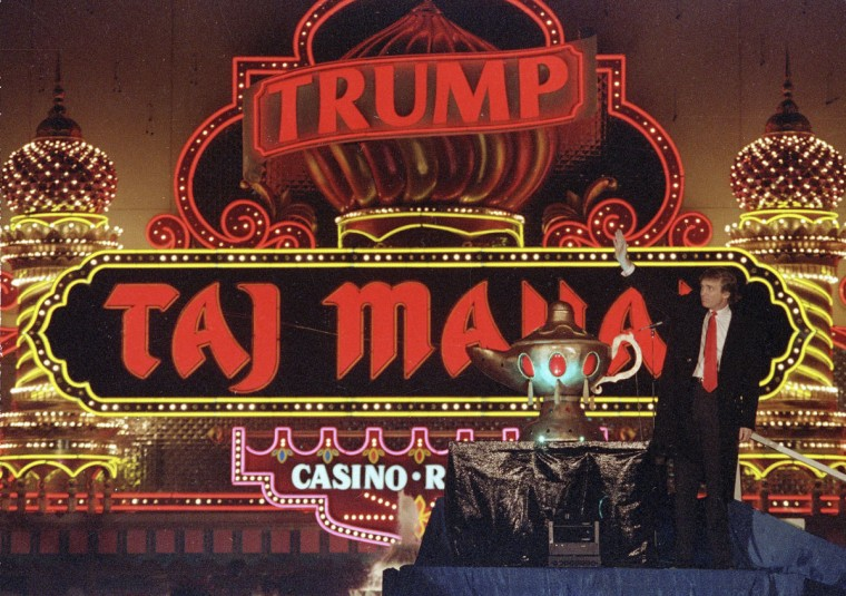 """In this April 5, 1990 file photo, Donald Trump stands next to a genie's lamp as the lights of his Trump Taj Mahal Casino Resort light up during ceremonies to mark its opening in Atlantic City, N.J. Trump opened his Trump Taj Mahal casino 26 years ago, calling it """"the eighth wonder of the world."""" But his friend and fellow billionaire Carl Icahn is closing it Monday morning, making it the fifth casualty of Atlantic City's casino crisis. (AP Photo/Mike Derer, File)"""