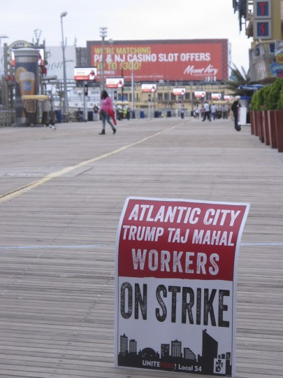 In this Oct. 5, 2016 photo, a striker's sign is displayed on the Boardwalk in Atlantic City, N.J., advising of a walkout against the Trump Taj Mahal casino. In the background is a billboard advertising a promotion from a Pennsylvania casino seeking business from Atlantic City customers. The Taj Mahal will shut down on Monday Oct. 10, 2016, the fifth Atlantic City casino to go out of business since 2014 due in large part to competition from casinos in neighboring states. (AP Photo/Wayne Parry)