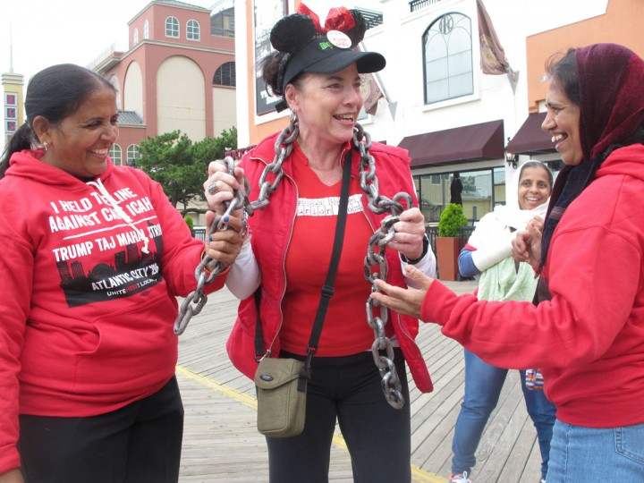 In this Wednesday, Oct. 5, 2016 photo, Tina Condos, center, greets fellow strikers outside the Trump Taj Mahal casino in Atlantic City N.J. while wearing chains to symbolize what she said were oppressive working conditions at the casino where she had worked since the day it opened in 1990. The casino is to close at 6 a.m. Monday Oct. 10, 2016, the fifth Atlantic City casino to go out of business since 2014. (AP Photo/Wayne Parry)