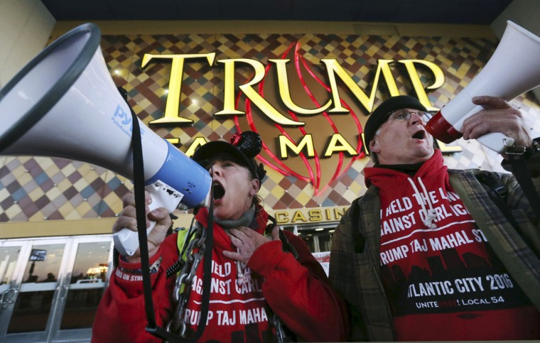 Members of Local 54 of the Unite-HERE union, Tina Condos, a cocktail waitress at Trump Taj Mahal and Keith Fullmer, a bartender, shout early in the morning outside the closing Trump Taj Mahal on Monday, Oct. 10, 2016, in Atlantic City, N.J. The sprawling Boardwalk casino, with its soaring domes, minarets and towers built to mimic the famed Indian palace, shut down at 5:59 a.m., having failed to reach a deal with its union workers to restore health care and pension benefits that were taken away from them in bankruptcy court. (AP Photo/Mel Evans)