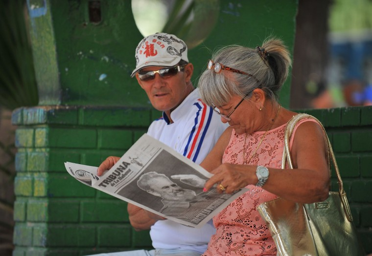 Cubans read a newspaper in a street of Havana, on November 27, 2016, two days after Cuban leader Fidel Castro died. Cuban revolutionary icon Fidel Castro died late November 25 in Havana, his brother, President Raul Castro, announced on national television. Castro's ashes will be buried in the historic southeastern city of Santiago on December 4 after a four-day procession through the country. (AFP PHOTO/YAMIL LAGE)