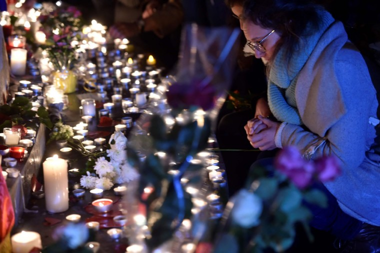 A woman looks on as people gather at a makeshit memorial at the bottom of the Marianne statue on place de la Republique in Paris on November 13, 2016 as France marked the first anniversary of the Paris attacks with sombre ceremonies and painful memories for the relatives of the 130 people killed. 130 people were killed on November 13, 2015 by gunmen and suicide bombers from the Islamic State (IS) group in a series of coordinated attacks in and around Paris. (AFP PHOTO / ALAIN JOCARD)