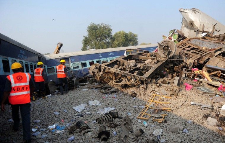 Indian rescue workers search for survivors in the wreckage of a train that derailed near Pukhrayan in Kanpur district on November 20, 2016. A passenger train derailed in northern India on November 20, killing at least 63 travellers most of whom were sleeping when the fatal accident occurred, police said. Rescue workers rushed to the scene near Kanpur in Uttar Pradesh state where the Patna-Indore express train derailed in the early hours of the morning. (AFP PHOTO / SANJAY KANOJIA)