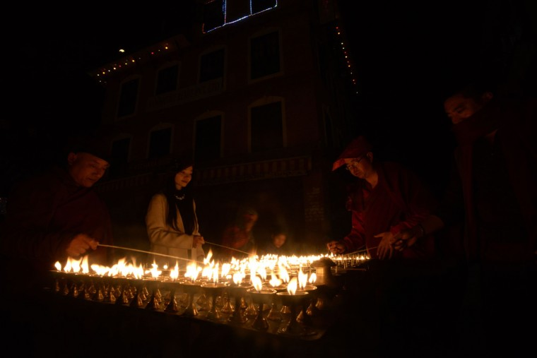 Buddhist devotees light butter lamps at Boudhanath Stupa on its reopening day following its renovation for earthquake damage on the outskirts of Kathmandu on November 22, 2016. Boudhanath Stupa was among hundreds of historic monuments damaged during the 7.8-magnitude quake that hit Nepal in April 2015 killing nearly 9,000 people. (Prakash Mathema/AFP/Getty Images)